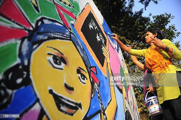 A Bangladeshi fine arts student paints on a wall in front of the Shahid Minar language movement mausoleum in Dhaka on February 20 as part of...