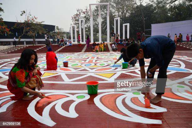 Bangladeshi fine arts students and teachers paint on the ground of the Central Shahid Minar in Dhaka on February 19 as part of preparations for the...