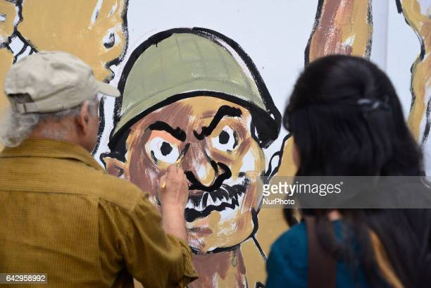 Bangladeshi fine arts students and teachers paints on a wall in front of the Central Shahid Minar in Dhaka on February 19 as part of preparations for...