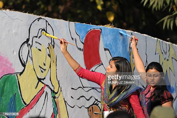 Bangladeshi fine arts students paint on a wall in front of the Shahid Minar language movement mausoleum in Dhaka on February 20 as part of...