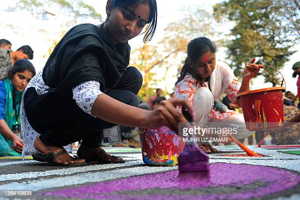 Bangladeshi fine arts students paint on the street in front of the Shahid Minar language movement mausoleum in Dhaka on February 20 as part of...