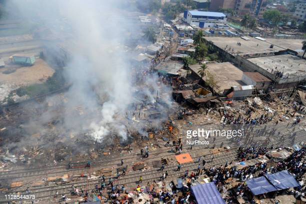 Bangladeshi fire Fighter and local people try to remove a fire broke out at Tejgaon slum in Dhaka Bangladesh on March 3 2019 More then fifty homes...