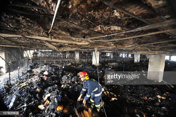 A Bangladeshi fire fighter inspects the 10th floor of the Hamim Group garment factory at Ashulia on December 15 2010 A raging fire on December 14...