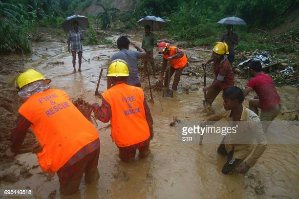 Bangladeshi fire fighters and residents search for bodies after a landslide in Bandarban on June 13 2017 Heavy monsoon rains have killed at least 46...