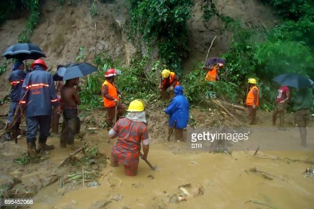 Bangladeshi fire fighters search for bodies after a landslide in Bandarban on June 13 2017 Heavy monsoon rains have killed at least 46 people in...