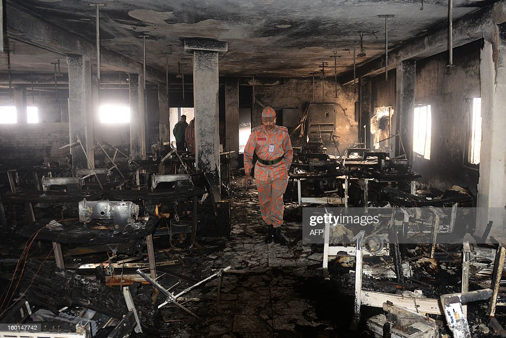 A Bangladeshi fire official inspects a burnt garment factory in Dhaka on January 27, 2013. At least seven female workers were killed on January 26 after a blaze swept through a small garment factory in the Bangladeshi capital of Dhaka, police and fire officials said. AFP PHOTO / Munir uz ZAMAN