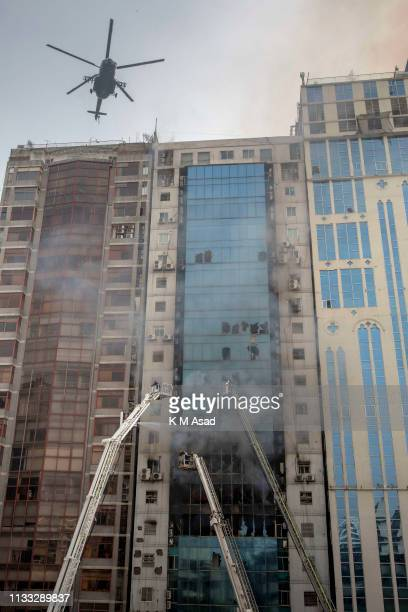Bangladeshi firefighter and an air force helicopter work to eclipse a blaze in a building Banani and rescue people A huge fire split through an...