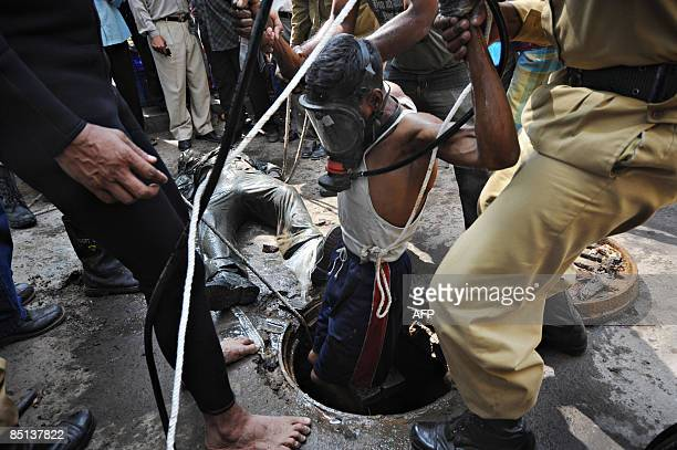 A Bangladeshi firefighter wearing a breathing apparatus exits a manhole after recovering a dead body of a Bangladesh Rifles officer near the Rifles...