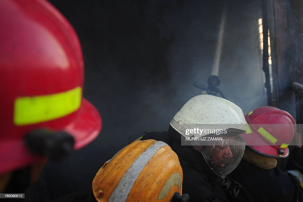 Bangladeshi firefighters attempt to extinguish a blaze at a garment factory in Dhaka on January 26, 2013. At least six workers at a garment factory in the Bangladeshi capital were killed in a stampede as a fire broke out. AFP PHOTO/Munir uz ZAMAN