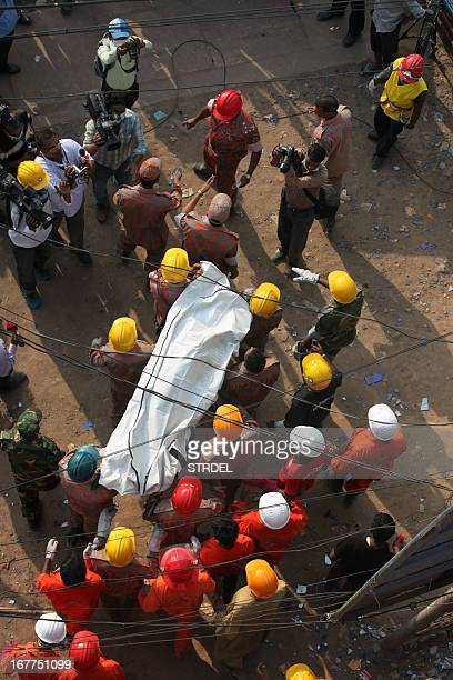 Bangladeshi firefighters carry the body of garment worker Shahana following her unsuccessful rescue from the eightstorey building that collapsed in...