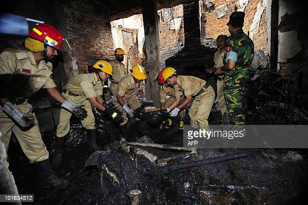 Bangladeshi firefighters inspect the site of a burntout house in Old Dhaka on June 5 2010 The national flag flew at halfmast and people of all faiths...