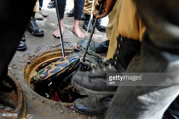 Bangladeshi firefighters recover the dead body of a Bangladesh Rifles officer from a manhole near the Rifles headquarters in Dhaka on February 27 two...