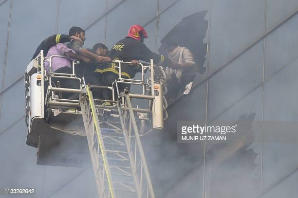 Bangladeshi firefighters rescue a person from a burning office building in Dhaka on March 28 2019 A huge fire tore through a Dhaka office block March...