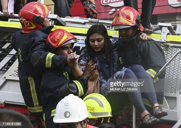Bangladeshi firefighters rescue a woman from a burning office building in Dhaka on March 28 2019 A huge fire tore through a Dhaka office block March...