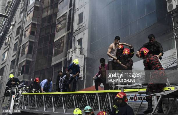 Bangladeshi firefighters rescue people from a burning office building in Dhaka on March 28 2019 A huge fire tore through a Dhaka office block March...