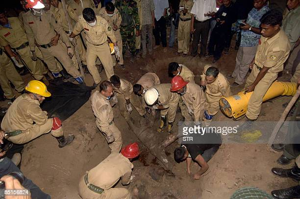 Bangladeshi firefighters retrieve the body of a Bangladesh Rifles officer from a mass grave inside the Rifles headquarters in Dhaka on February 27...