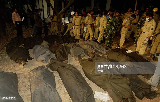 Bangladeshi firefighters stand beside the bodies of Bangladesh Rifles soldiers retrieved from a mass grave inside the Rifles headquarters in Dhaka on...