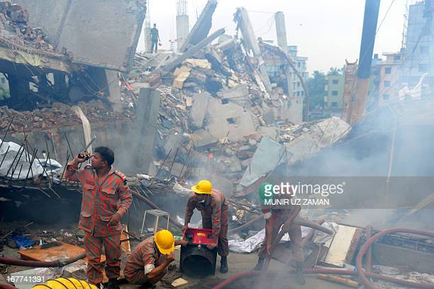 Bangladeshi firefighters try to control a blaze after a fire broke out during a rescue attempt of a woman as Bangladeshi Army personel begin the...