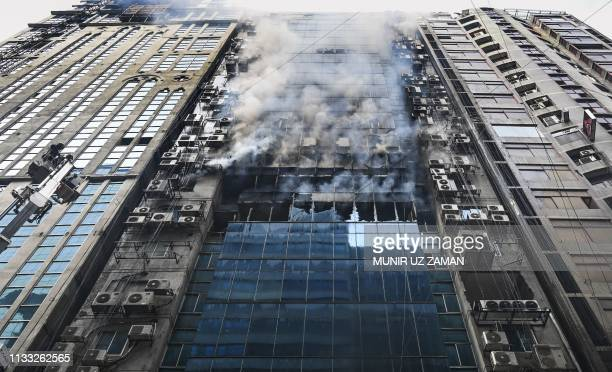Bangladeshi firefighters try to extinguish a blaze in an office building in Dhaka on March 28 2019 A huge fire tore through a Dhaka office block...