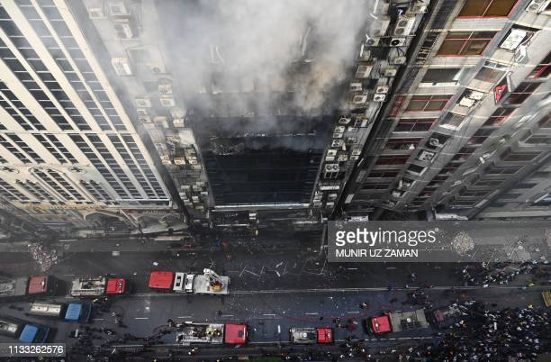 TOPSHOT Bangladeshi firefighters try to extinguish a blaze in an office building in Dhaka on March 28 2019 A huge fire tore through a Dhaka office...
