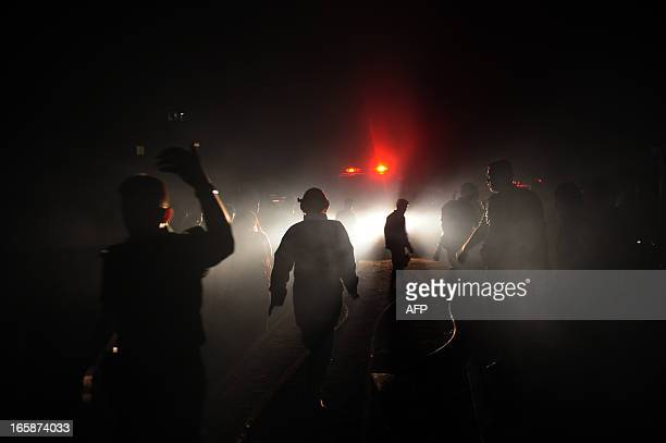 Bangladeshi firefighters walk past lights as they attempt to extinguish a blaze at a market in Dhaka on April 7 2013 More then 100 shops were raized...