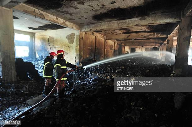 Bangladeshi fire-men extinguish a fire in the nine-storey Tazreen Fashion plant in Savar, about 30 kilometres north of Dhaka on November 25, 2012....