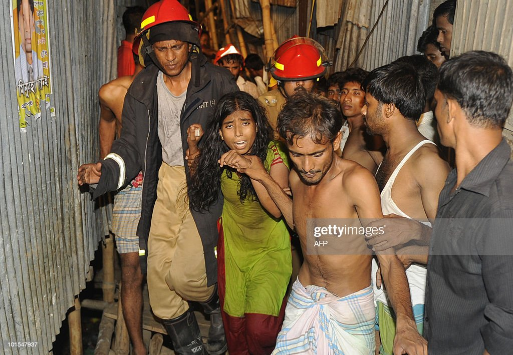 Bangladeshi firemen lead a rescued girl, Hena (C), from the site of a collapsed four-storey building in Dhaka late on June 1, 2010. A four-storey building collapsed late on June 1 and fell on several tin-roofed shanties in Dhaka, trapping an unknown number of people, police and fire officials said.