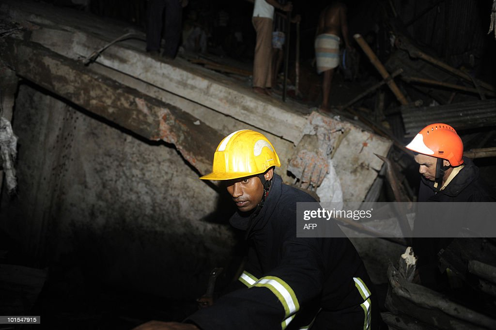 Bangladeshi firemen look for trapped survivors after a four-storey building collapsed in Dhaka late on June 1, 2010. A four-storey building collapsed late on June 1 and fell on several tin-roofed shanties in Dhaka, trapping an unknown number of people, police and fire officials said.