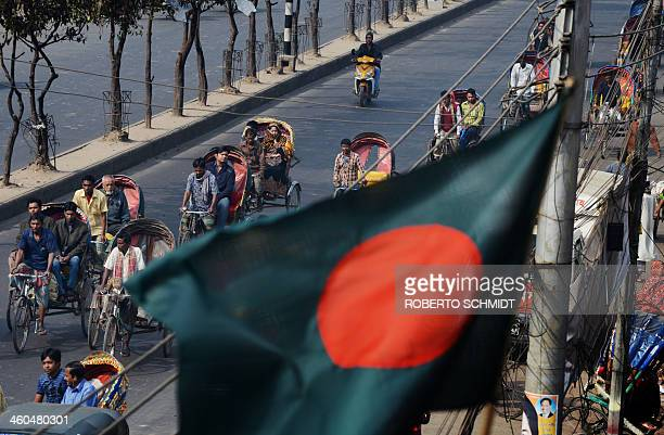 A Bangladeshi flag flutters in the wind as cycle rickshaw drivers ferry commuters down an avenue in Dhaka on January 4 2014 It is estimated that...