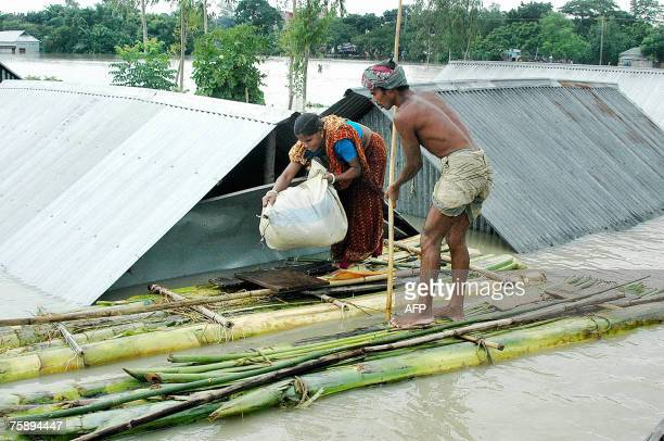 Bangladeshi flood affected couple use a raft made of banana trees to navigate to shelter in the Sirajgonj District, some 105 kms north-west of Dhaka,...