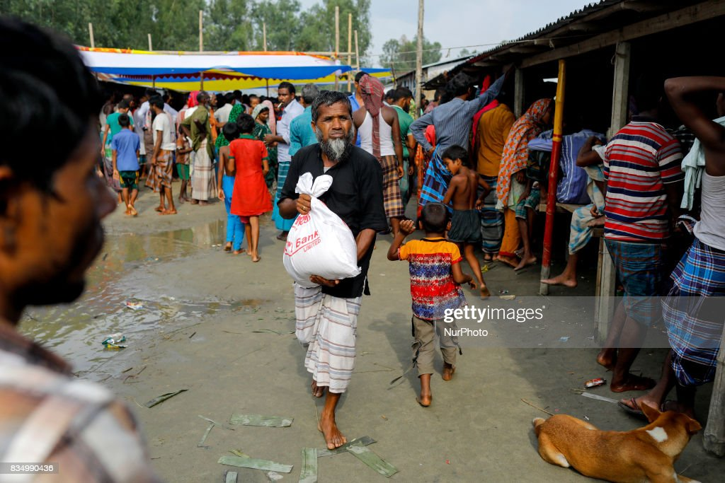 Bangladeshi flood affected men receive relief from a local rulling party MP at Jamtola, Sariakandi, Bogra, Bangladesh 17 August 2017. According to authorities, floods caused by heavy rainfall lashing Bangladesh during the past week have left at least 56 people dead. Affected people are waiting to get more relief as they are in shortage of food and drinking water in the shelter centers.