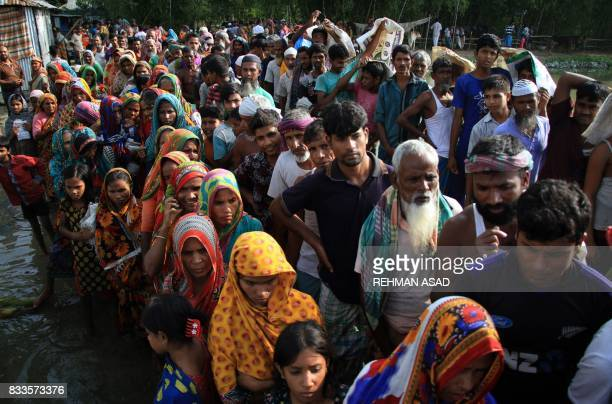 Bangladeshi flood victims wait in a queue for relief materials in Kurigram on August 17 2017 Two Bangladeshi teenagers have died taking selfies in...