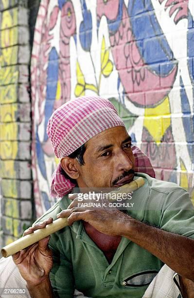 Bangladeshi flute vendor plays a bamboo flute on a street near The Fine Art University in Dhaka 28 November 2003 Many Bangladeshi's earn a living by...