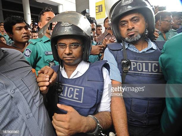 Bangladeshi garment factory owners Aminul Islam and Masudur Rahaman clad in policeissue body armour and helmet are escorted for their appearance at...