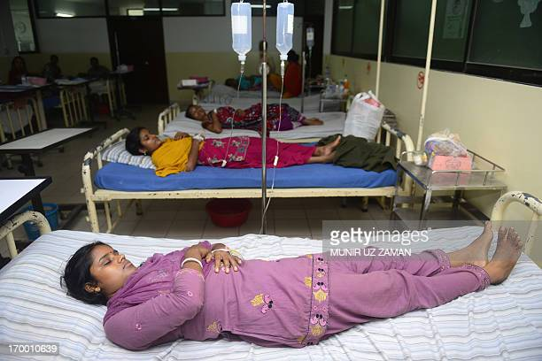 Bangladeshi garment factory workers receive medical treatment after falling sick from drinking contaminated water on the outskirts of Dhaka on June 6...