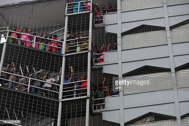 Bangladeshi garment workers look on from a factory as other garment works protest on the street below in Dhaka on September 23 2013 Angry Bangladeshi...