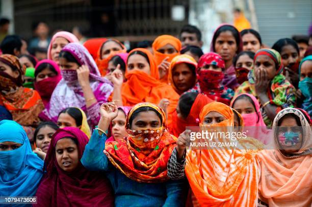 Bangladeshi garment workers shout slogans as they block a road during a demonstration to demand higher wages in Dhaka on January 9 2019 Bangladeshi...
