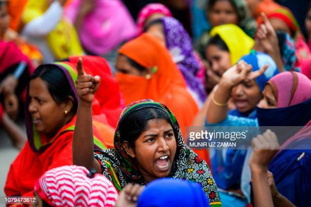 TOPSHOT Bangladeshi garment workers shout slogans as they block a road during a demonstration to demand higher wages in Dhaka on January 9 2019...