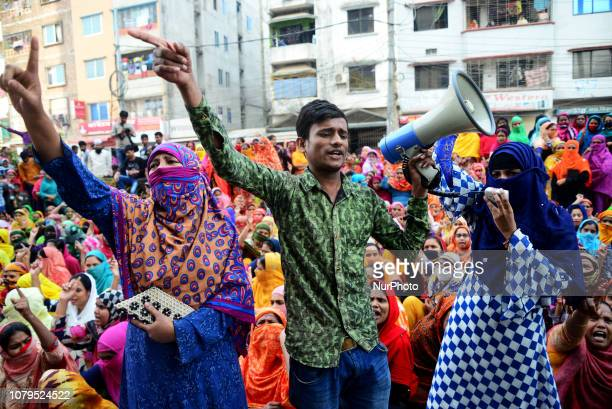 Bangladeshi garment workers shout slogans as they block a road during a demonstration to demand higher wages in Dhaka Bangladesh on January 9 2019...