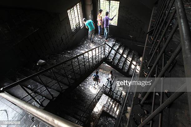 Bangladeshi garment works walk on the burnt stairs of the nine-story Tazreen Fashion plant in Savar, about 30 kilometres north of Dhaka on November...