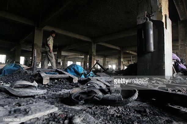 Bangladeshi garment works walk past debris on the floor of the ninestory Tazreen Fashion plant in Savar about 30 kilometres north of Dhaka on...