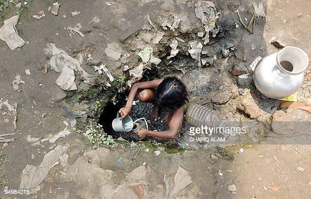 A Bangladeshi girl collects drinking water from a hole in the ground in Dhaka 22 March 2006 on the World Water Day The United Nations warned that...