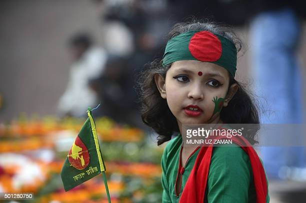 Bangladeshi girl holds a national flag as people gather to pay homage at the Intellectual Martyrs Memorial in Dhaka on December 14 2015 Thousands of...