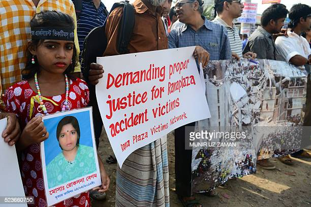 A Bangladeshi girl holds a photo of her mother who died in the Rana Plaza building collapse during a protest march on the third anniversary of the...