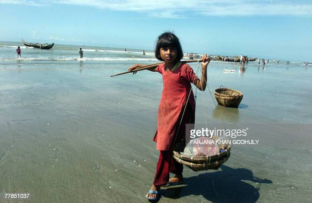 A Bangladeshi girl roams around the shore of the Bay of Bengal to collect leftover fish from the fishermen's nets in Teknaf southern most tip of...