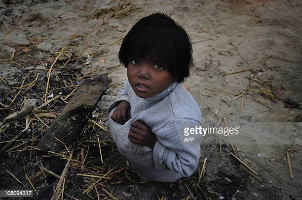 A Bangladeshi girl sits next to a bonfire as she warms herself in a slum area in Dhaka on January 13 2011 Cold wind and dense fog battering the...