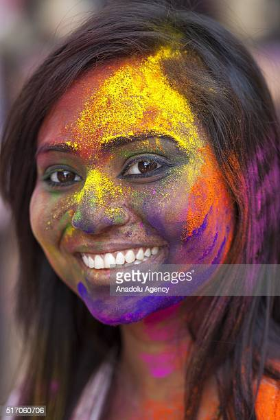 Bangladeshi girl whose face is covered with colored with colored powders during Holi celebrations in Dhaka Bangladesh on March 23 2016 Holi is the...