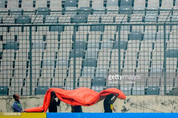 Bangladeshi ground men carry plastic cover during the fourth day of a Test cricket match between Bangladesh and Zimbabwe at the ShereBangla National...