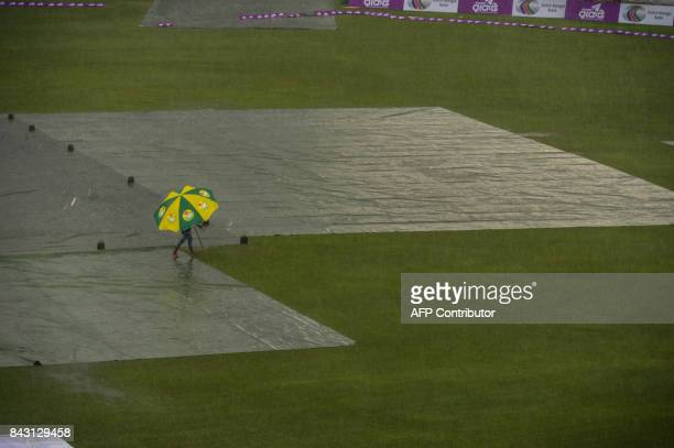 A Bangladeshi ground staff walks over the field as the match si delayed due to rain during the third day of the second cricket Test match between...