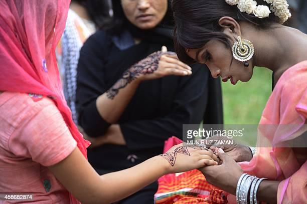A Bangladeshi hijra transgender applies henna on a woman's hand as a part of the first ever nationwide program to observe 'Hijra Day' to be held on...